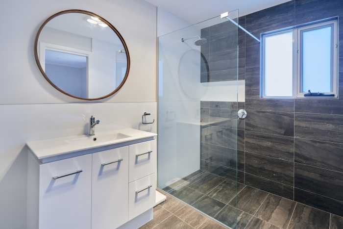 Large bathroom with white vanitie and black tiles