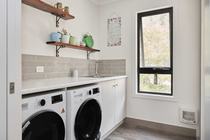 Large laundry with beige tiled splashback