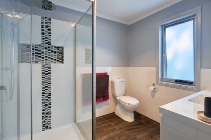 Bathroom with tiled niche and blue walls of prefabricated home