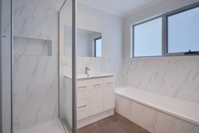 Clean white bathroom with shower at Waterhouse