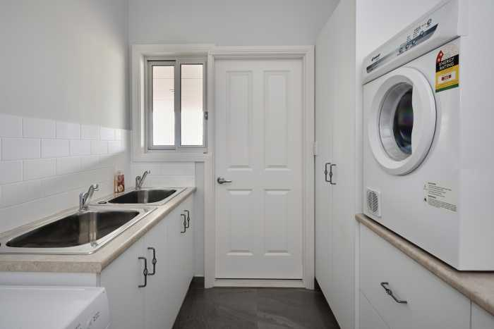 Traditional white and cream laundry with two sinks at Clarence Point