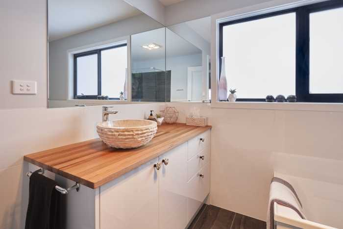 Wooden vanity top with natural cream stone sink at Bellbuoy Beach