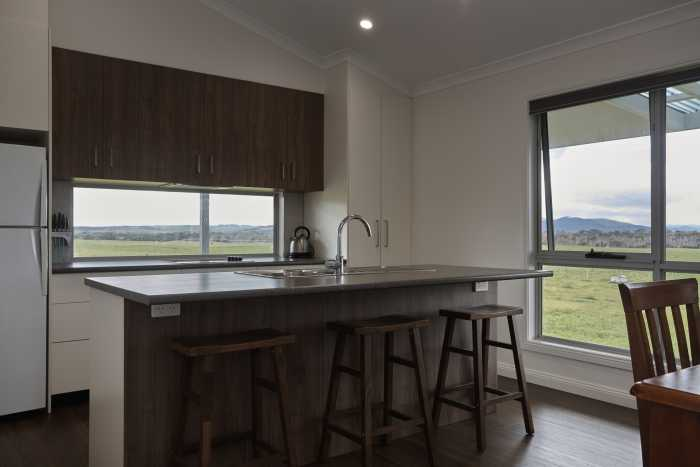 Open plan kitchen with timber cupboards at Waterhouse
